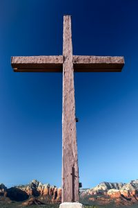 A large wooden cross set against a brilliant blue sky with colorful distant mountains stands as a testament to faith.